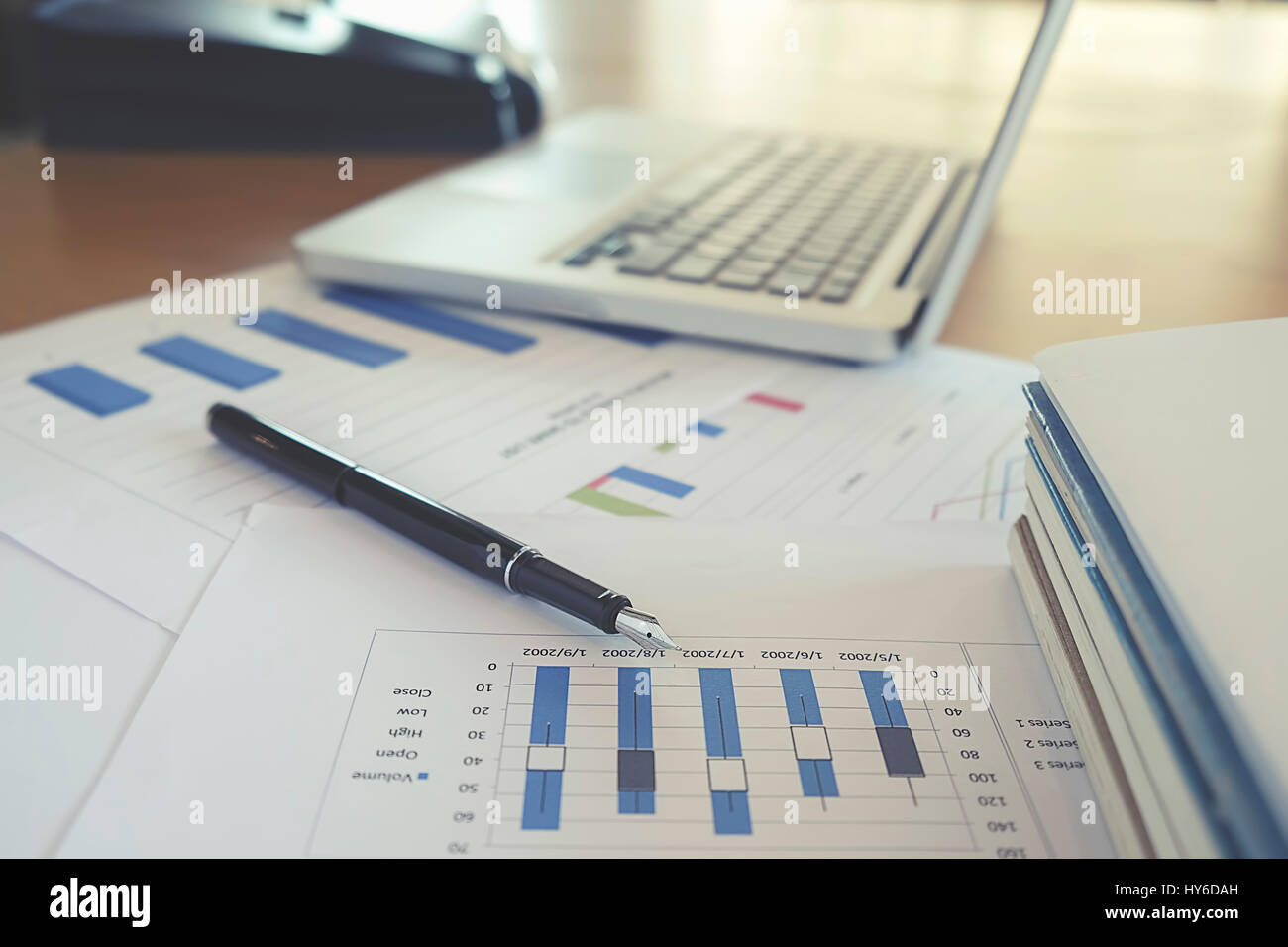 Business concept with copy space. Office desk table with pen focus and analysis chart, computer, notebook, cup of - Stock Image