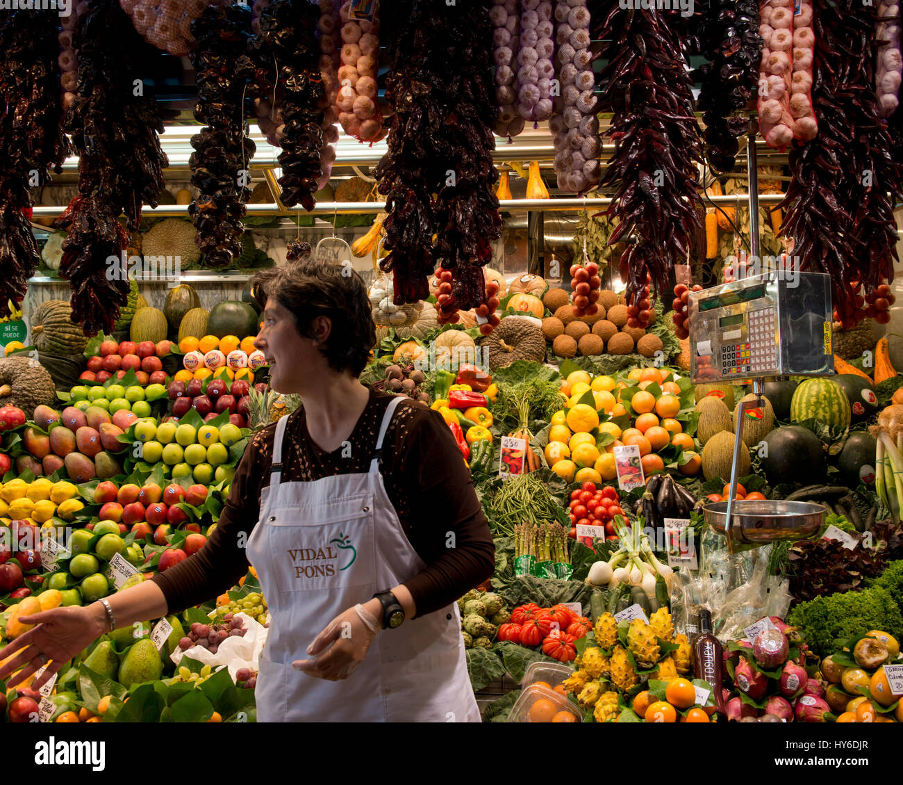 Woman gesticulating in front of fruit market stall at La Boqueria Market, Las Ramblas, Barcelona, Catalonia, Spain - Stock Image