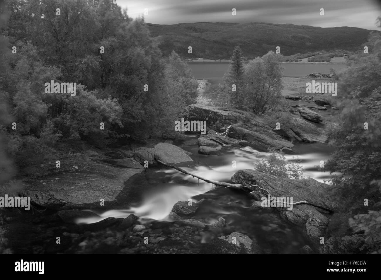 Water stream flowing down to a sea in Sjona, near Mo i Rana, Norway - Stock Image