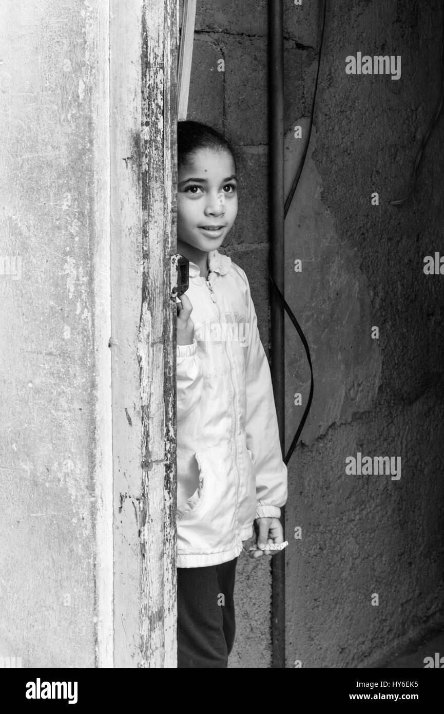 Young girl peeking through a doorway in old Havana, Cuba. - Stock Image