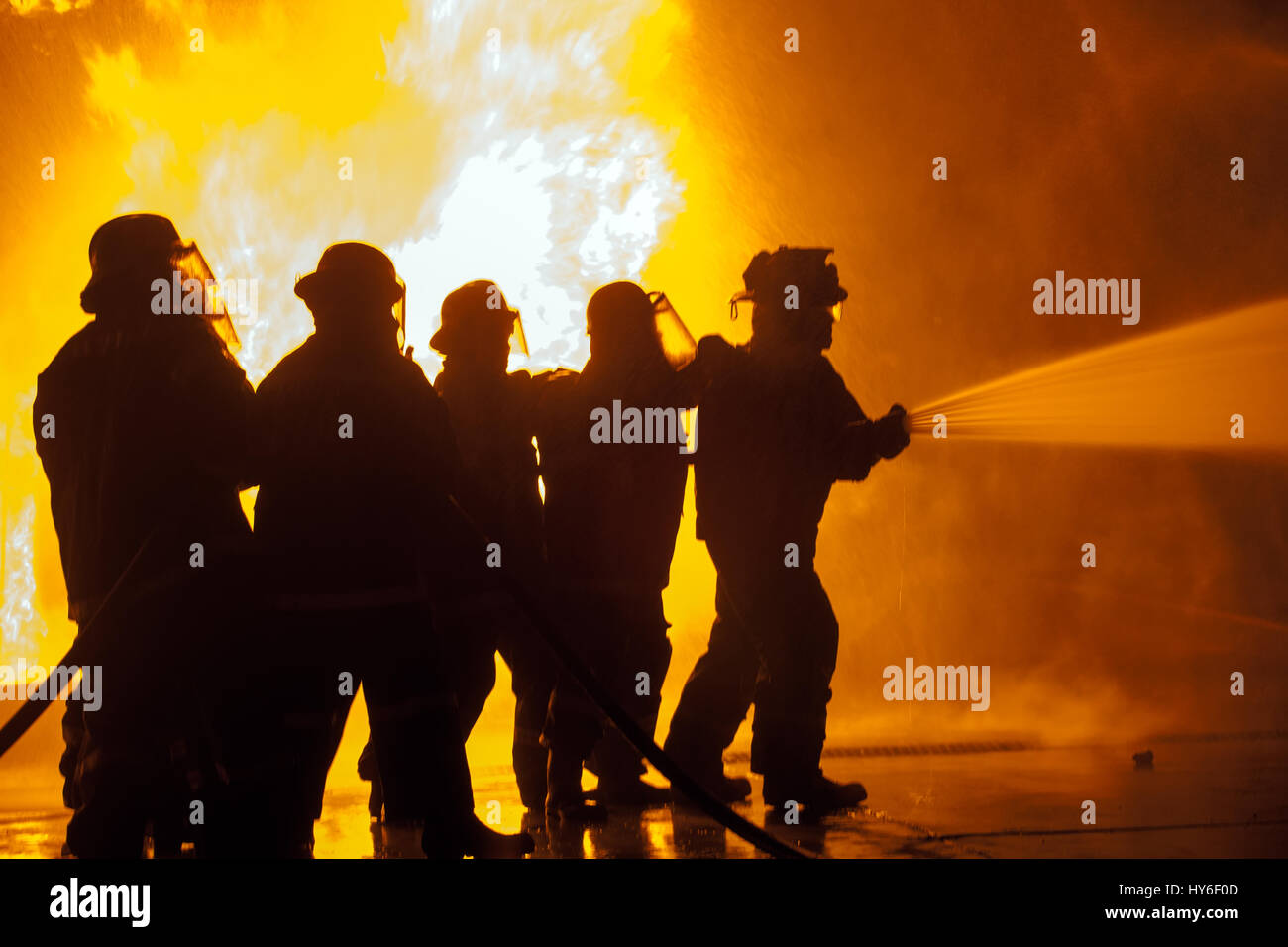 Group of firefighters controlling hose spraying water during firefighting exercise Stock Photo