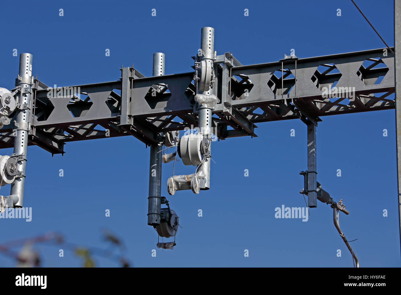 Newly installed O H L E Over Head Line Equipment on a gantry showing the Catenary and conductor wire tensioners - Stock Image