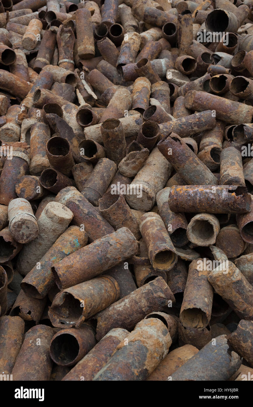 A large pile of empty shrapnel shell cases from WW1 waiting to be recycled in a metal recycling yard Stock Photo