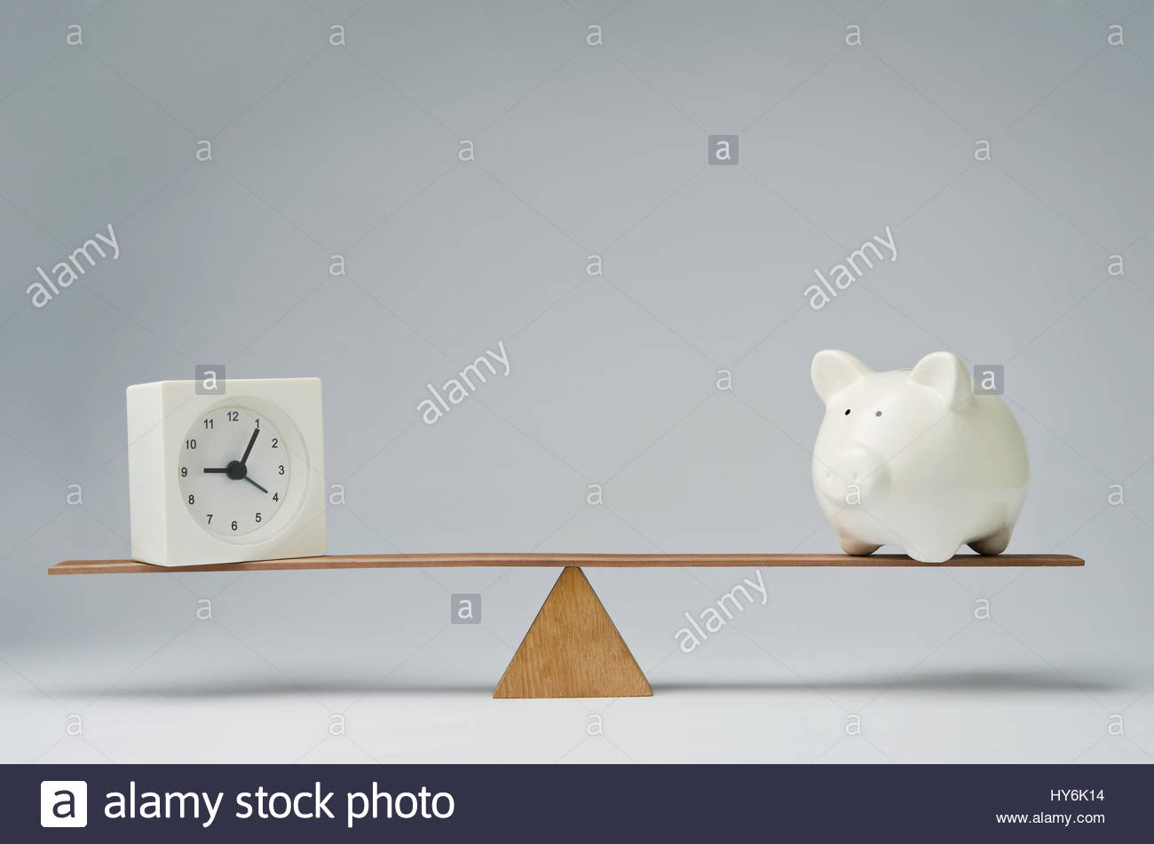 Clock and piggy bank balancing on a seesaw - Stock Image
