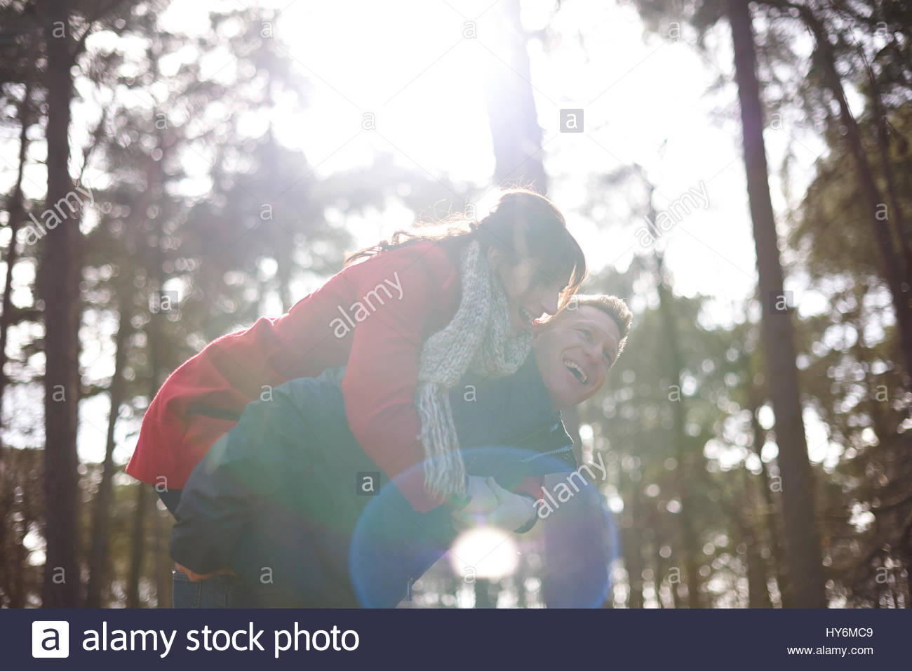 young man giving young lady a piggy back - Stock Image
