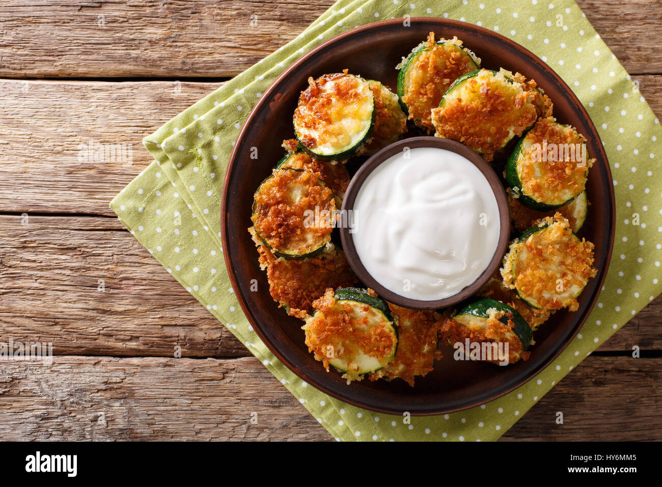 Zucchini in breaded Panko with sour cream close-up on the table. horizontal view from above - Stock Image