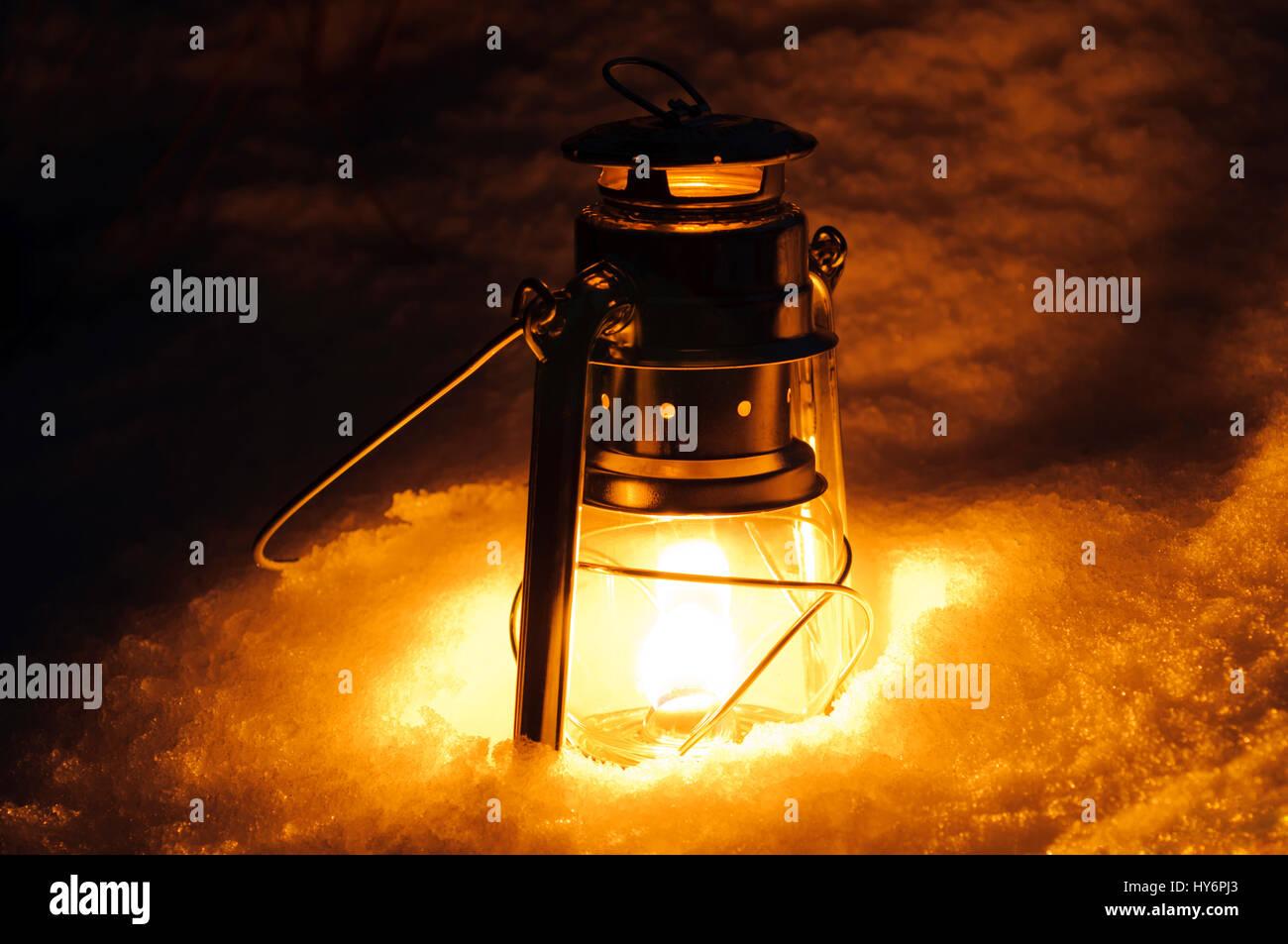 Kerosene lamp in the snow at night. - Stock Image
