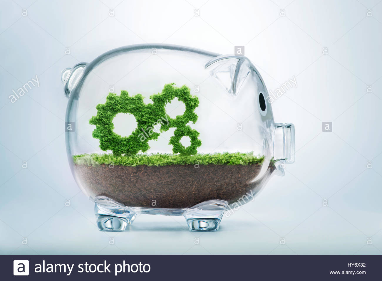 Business growth concept with grass growing in shape of gears inside transparent piggy bank - Stock Image