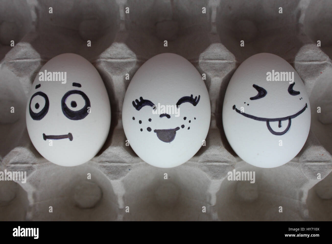Eggs with faces photo for your design. in the box. Funny and cute. Three eggs love triangle - Stock Image