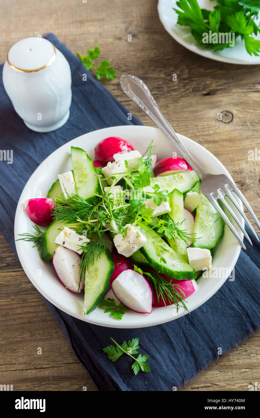 Spring vegetable salad with fresh cucumber, radishes, feta cheese, herbs, sprouts in bowl on wooden background  - Stock Image
