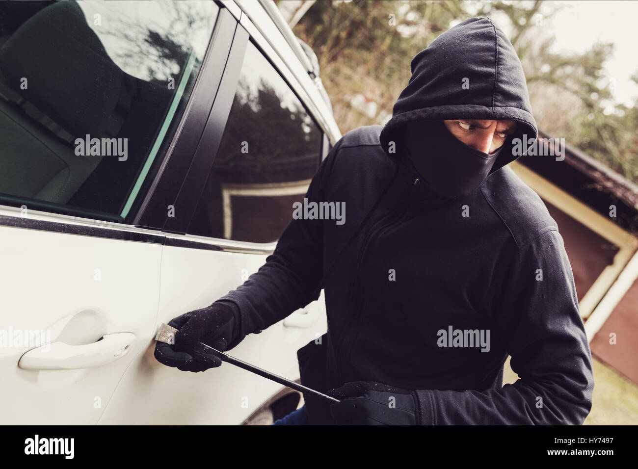 car theft - thief trying to break into the vehicle - Stock Image