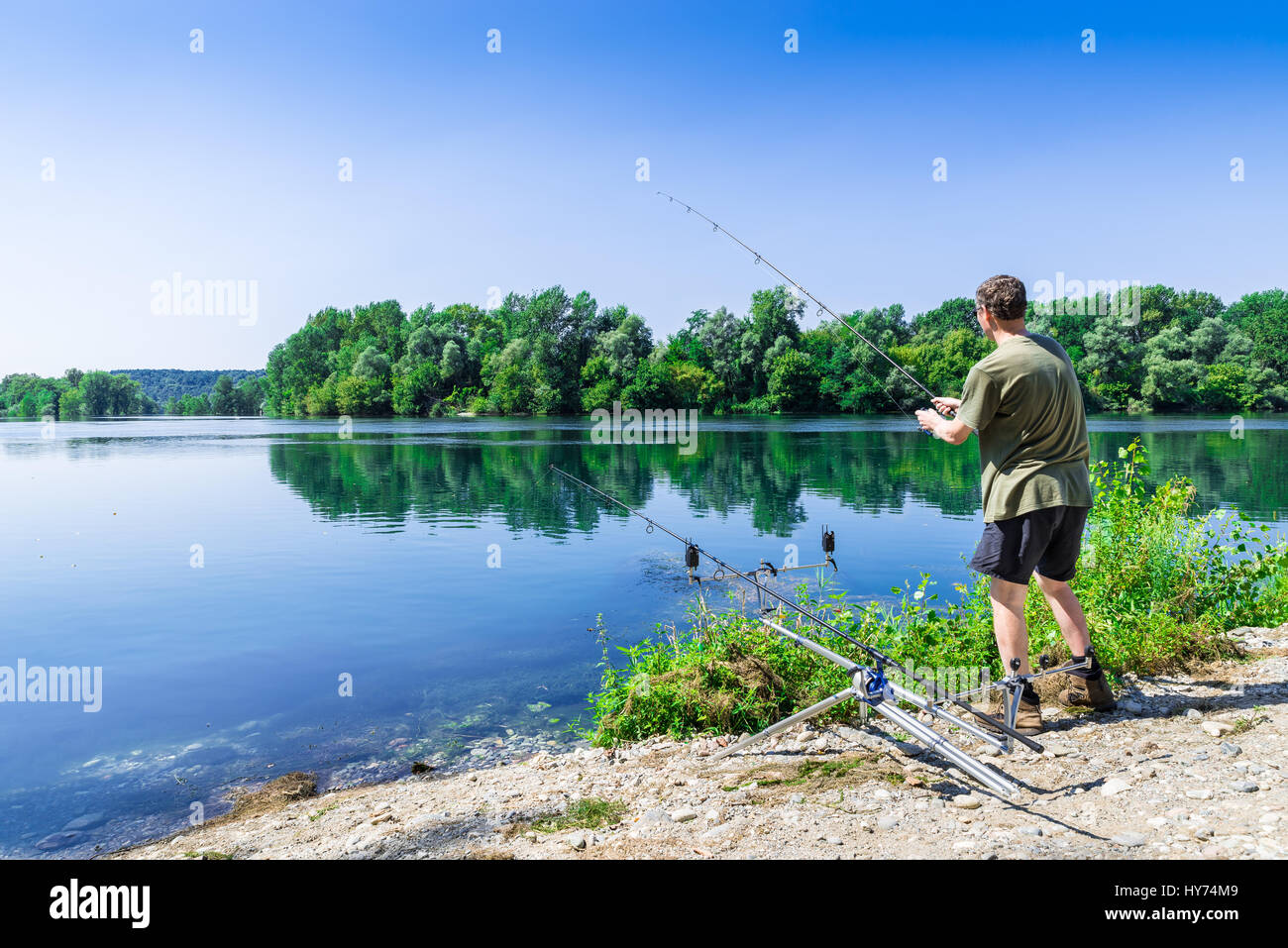 Fishing adventures, carp fishing. Angler is fishing with carpfishing technique in freshwater, in a beautiful summer - Stock Image