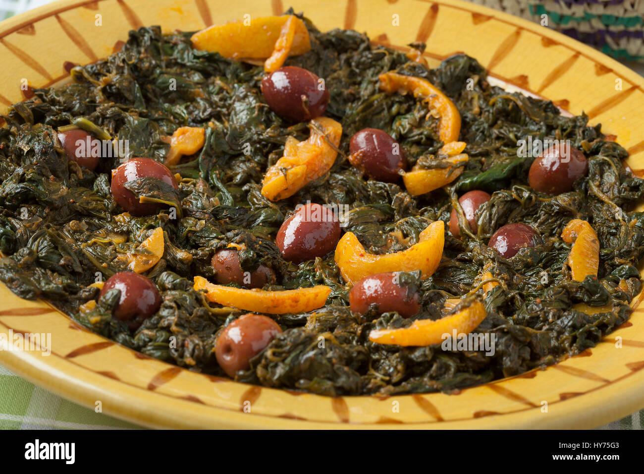 Traditional Moroccan dish with spinach, olives and preserved lemon close up - Stock Image