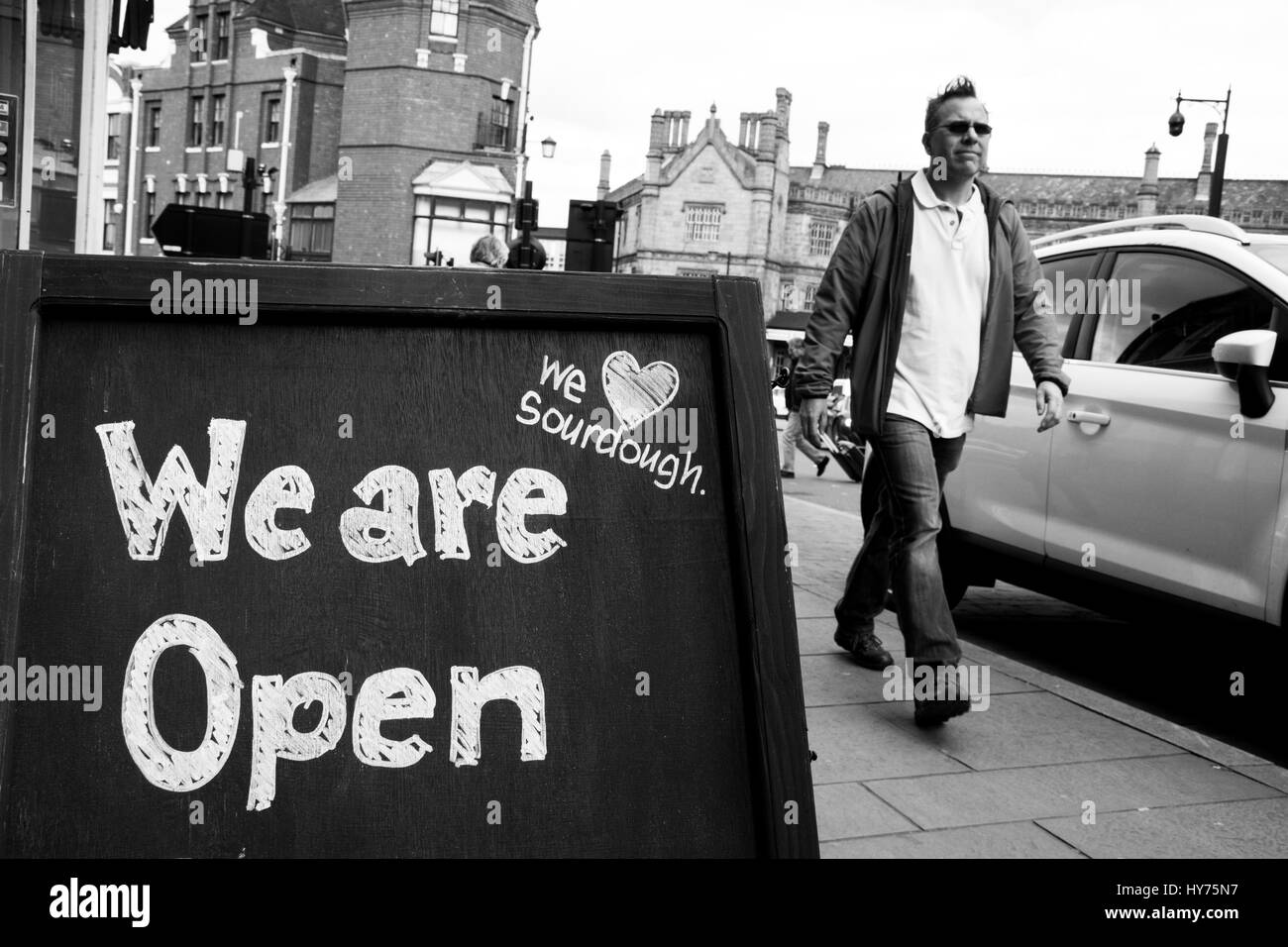 Chalkboard sign saying, 'We are open'.  Outside an independent bakery in Shrewsbury. - Stock Image
