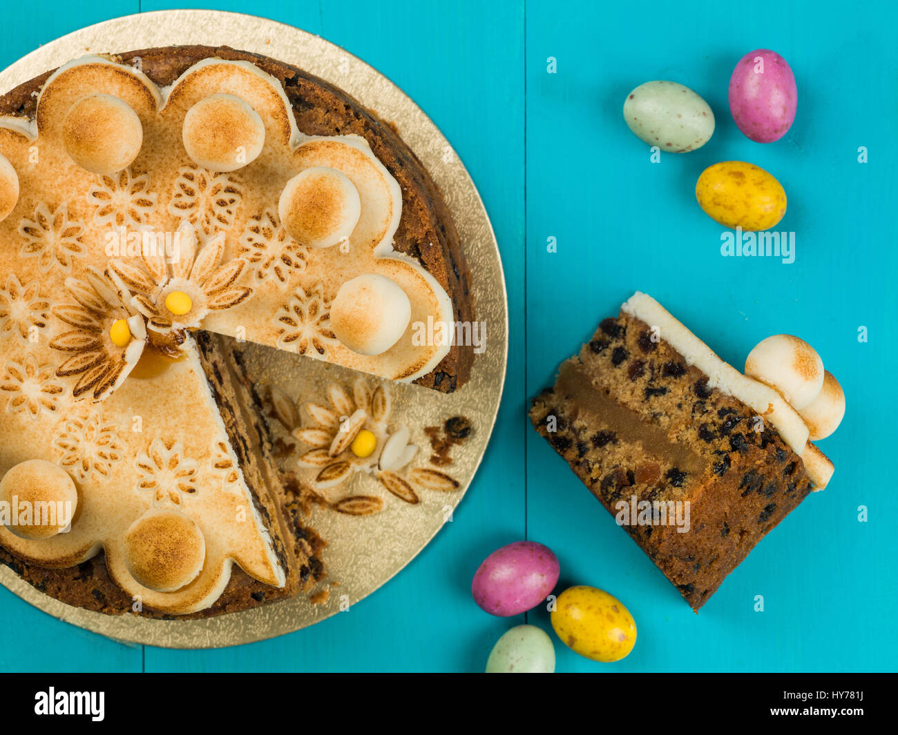 Easter Simnel Cake With Marzipan Icing and Decorations Against a Blue Background - Stock Image