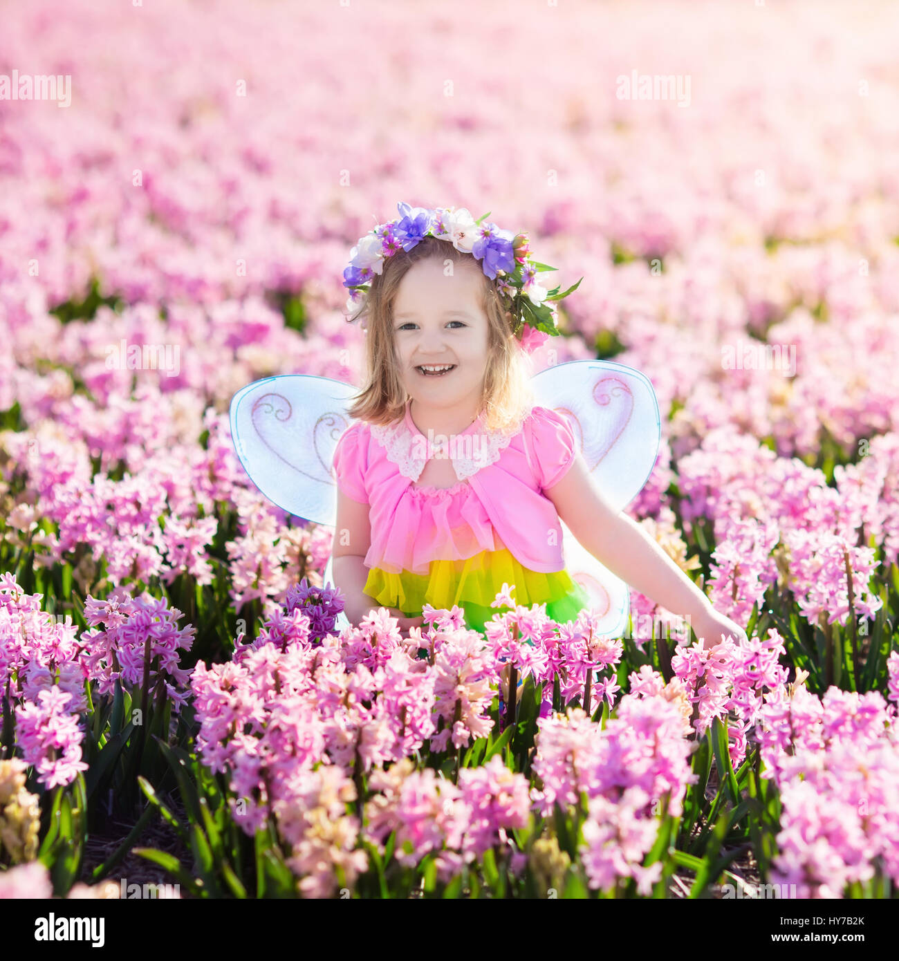 Beautiful Girl Playing In Blooming Hyacinth Flower Field. Kids Princess  Birthday Party With Fairy Costume, Butterfly Wings And Magic Wand. Children  Pl
