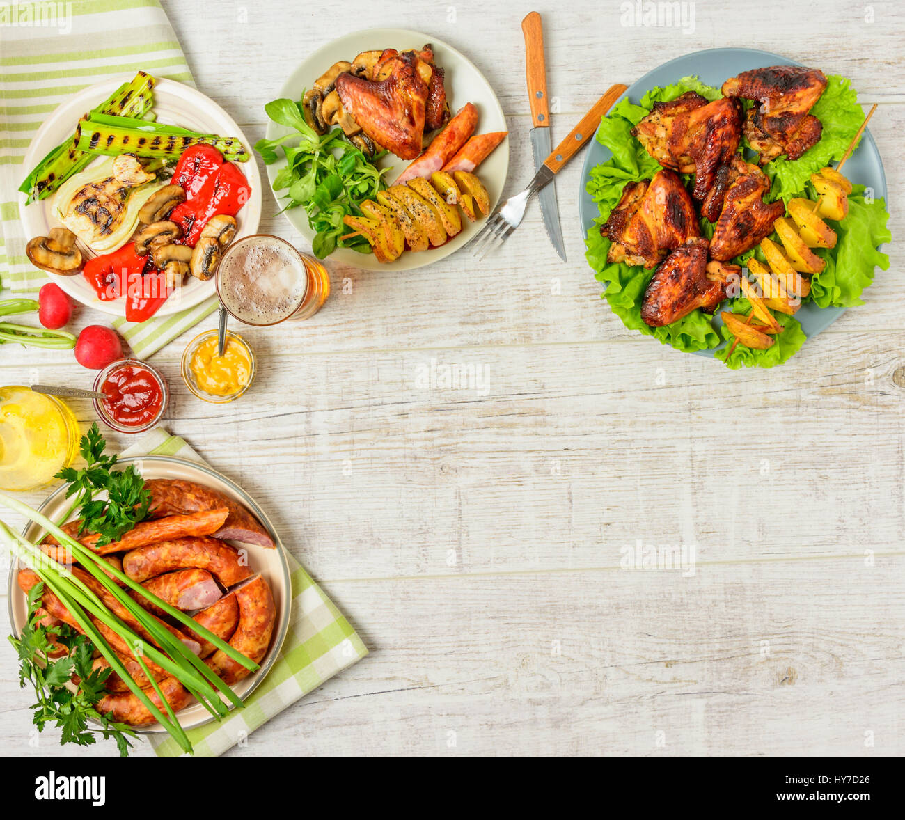 Dinner table with variety food, fried chicken wings, sausages, grilled vegetables in a pan, salad and  lager beer Stock Photo