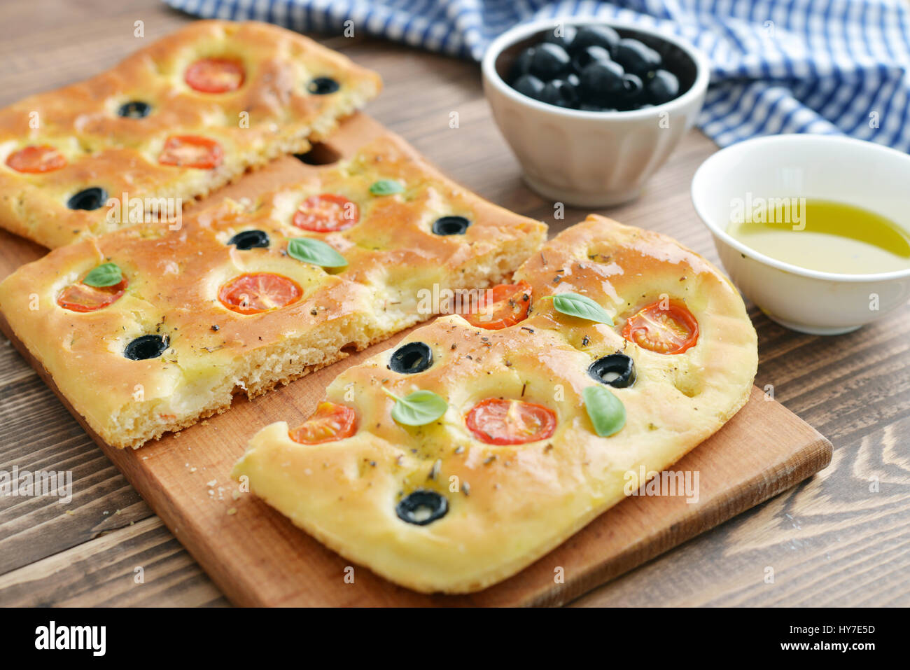 Italian food -  traditional focaccia with cherry tomato and olives on wooden background - Stock Image