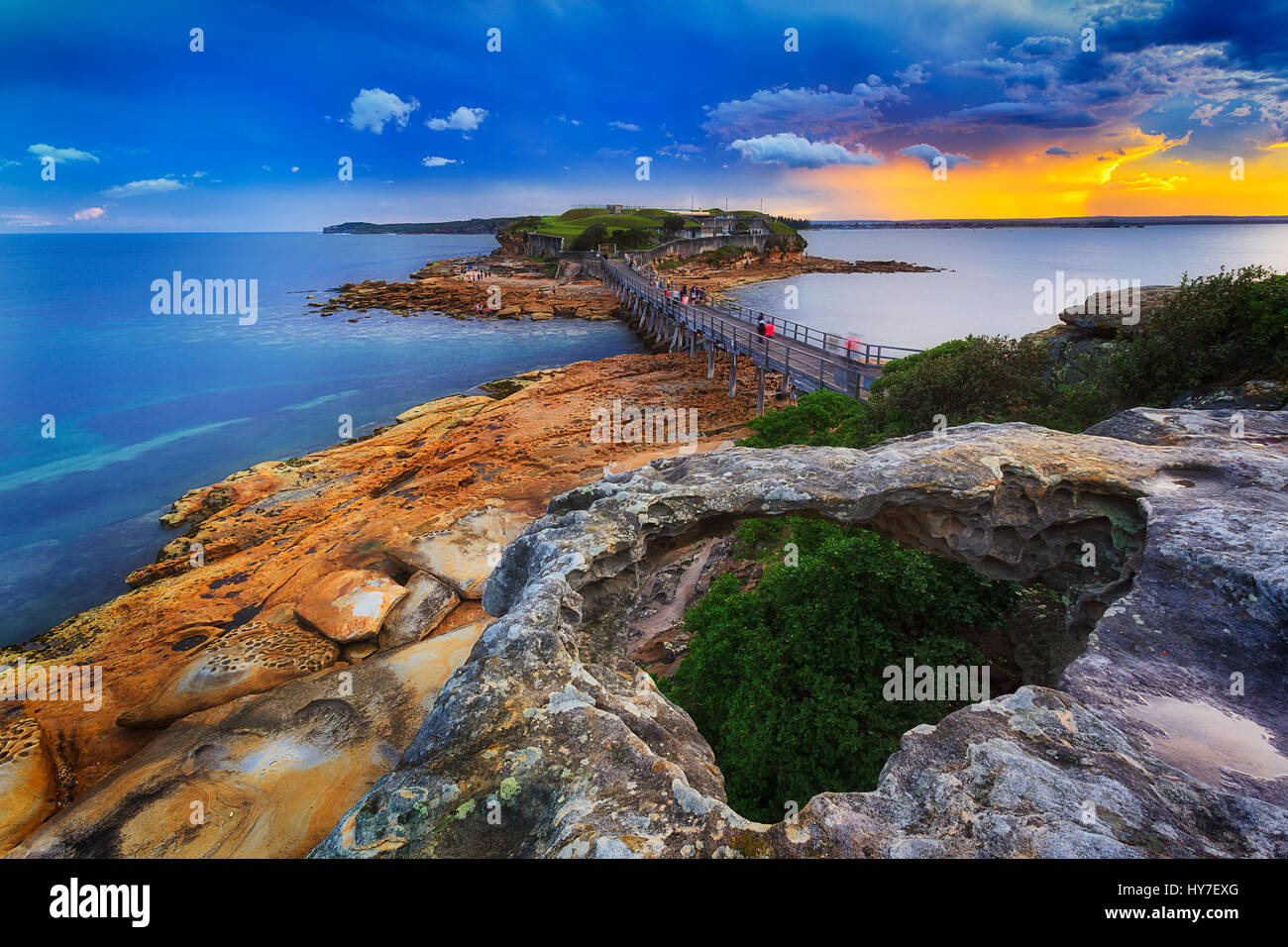Colourful sunset over Citadel on Bare Island in Sydney's Botany Bay coastal area. Stormy weather and rugged - Stock Image