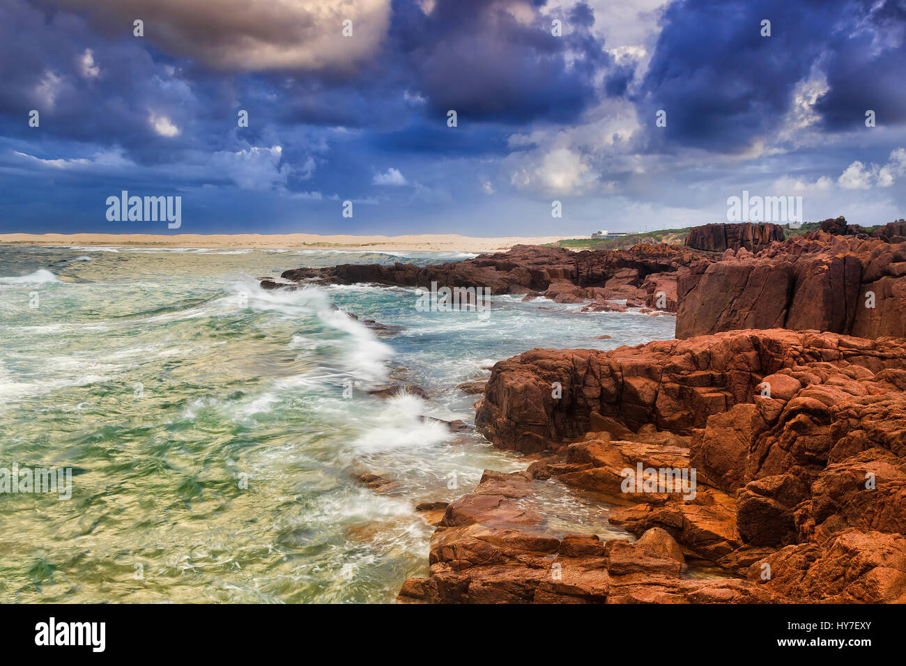 Rugged rocky coast transitioning to sand dunes and beach at stormy sunrise near Port Stephens, NSW, Australia. - Stock Image