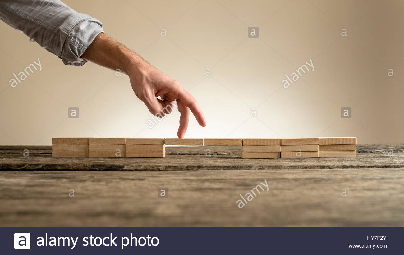 Man hand showing walking fingers over fragile bridge of wooden bricks on table surface on sepia toned background, - Stock Image