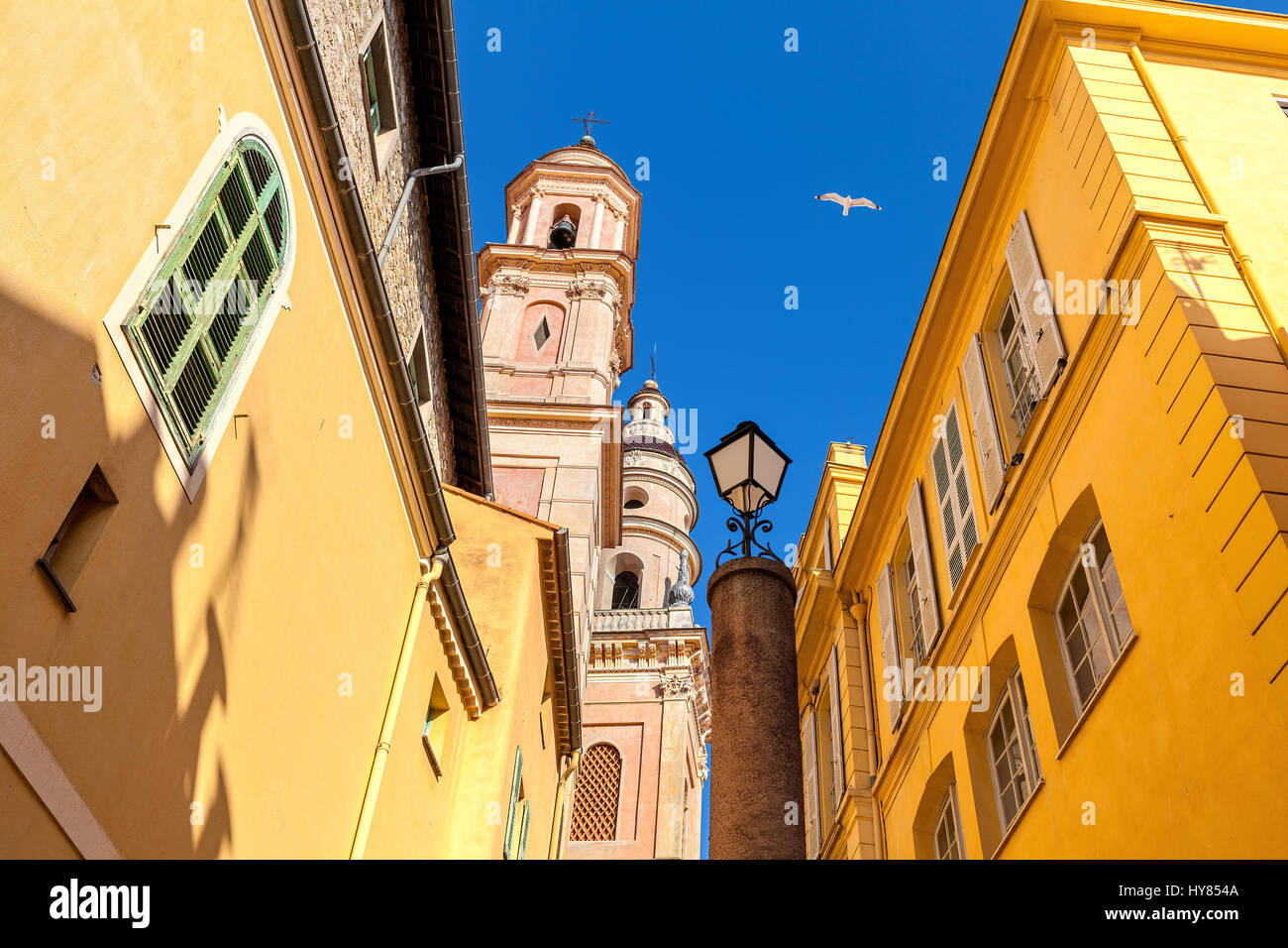 Belfry of Saint-Michel Archange basilica among colorful houses under blu sky in old town of Menton, France. Stock Photo