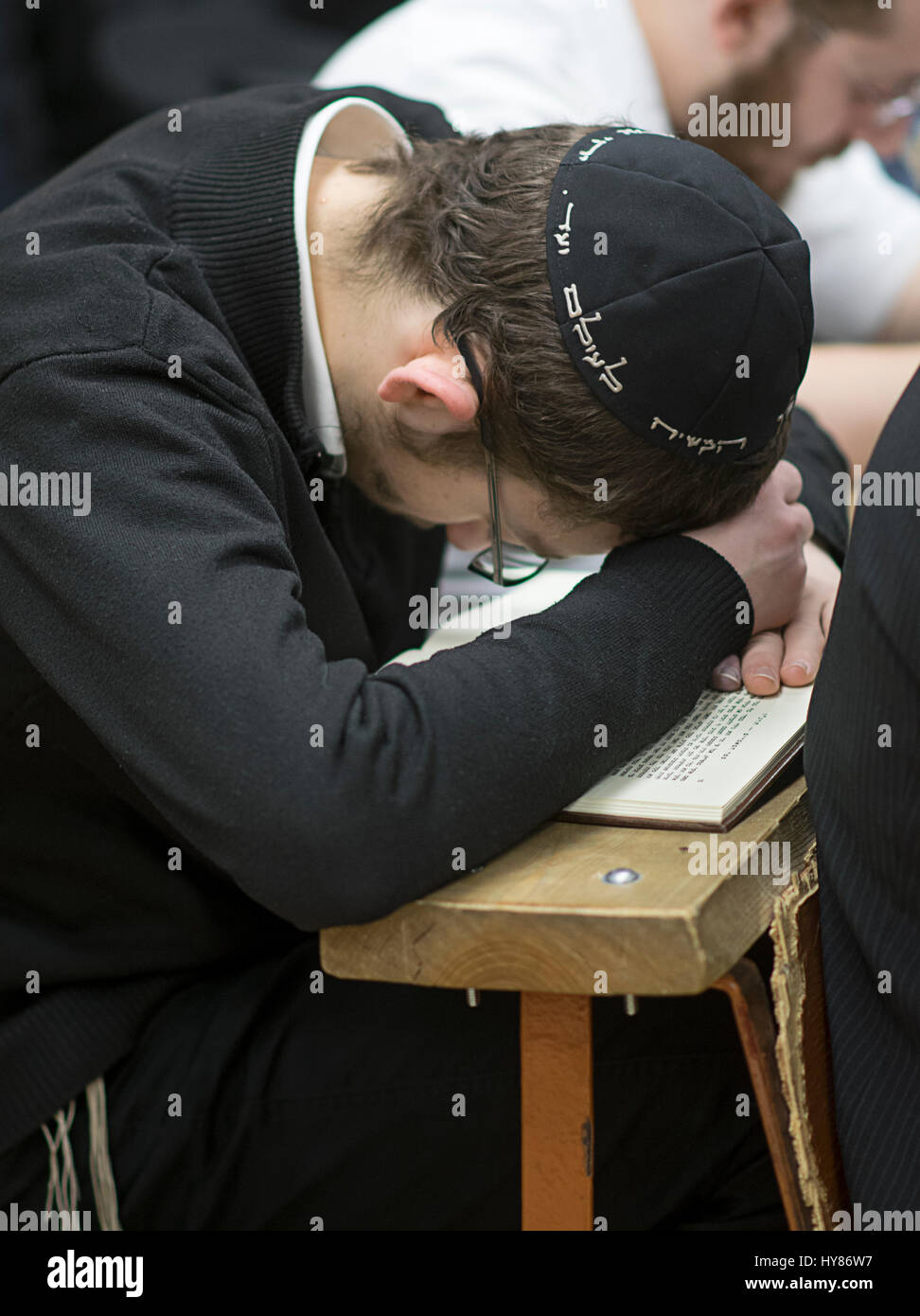 An unidentified religious Jewish boy studying alone from a Hebrew book in a synagogue in Brooklyn, New York. - Stock Image