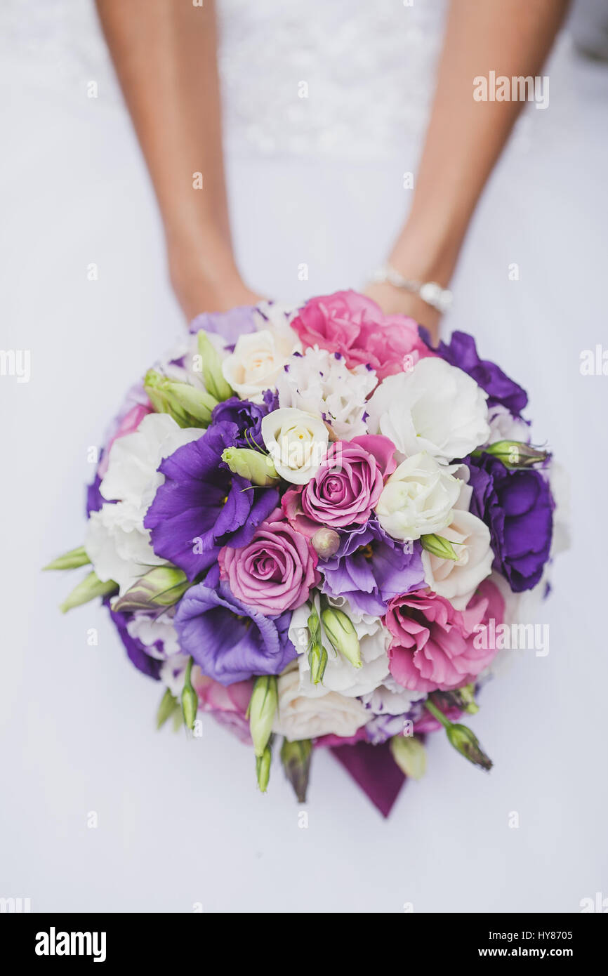 Bride In A White Wedding Dress Holding A Flowers Bouquet From