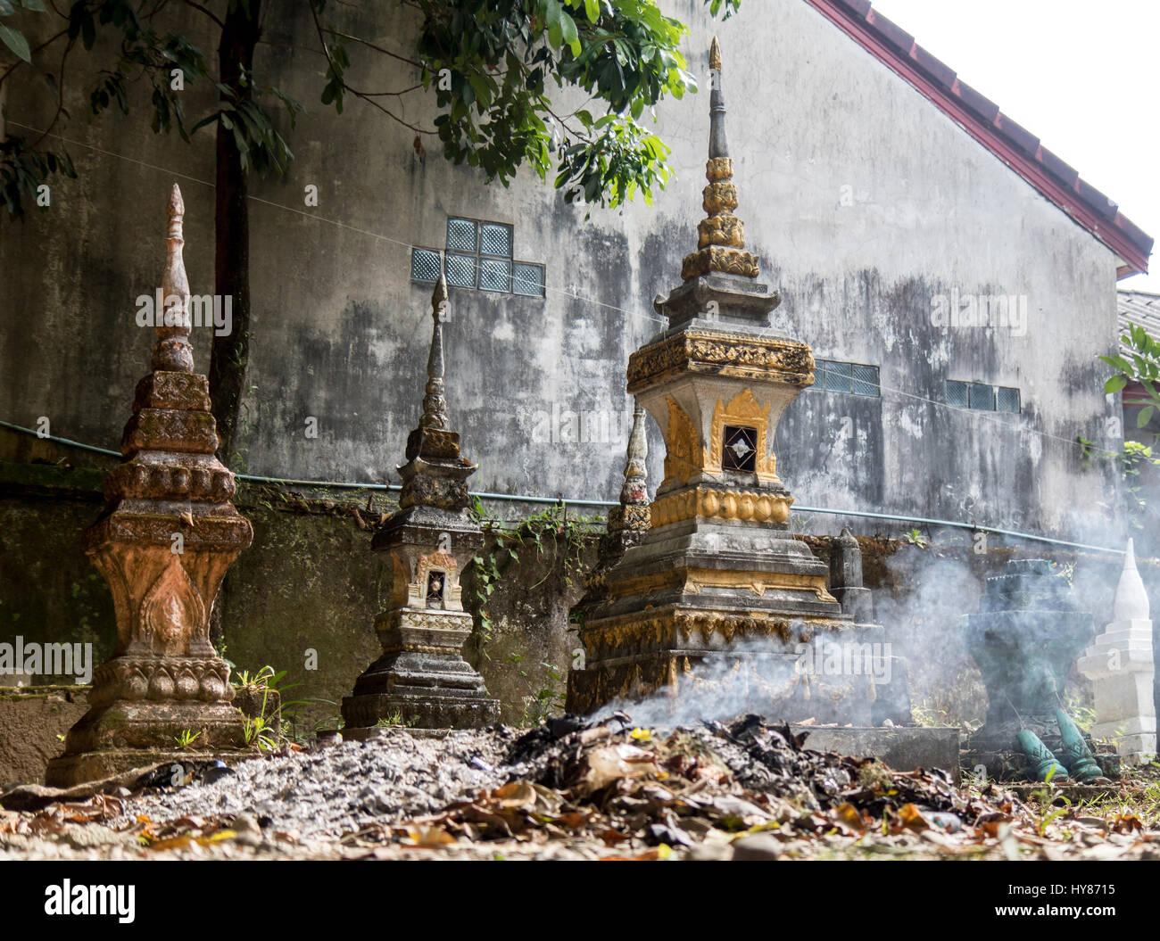 burning waste at the ossuary at a Buddhist monastery Wat Si Sou Mang , Vang Vieng, Vientiane Province, Laos - Stock Image