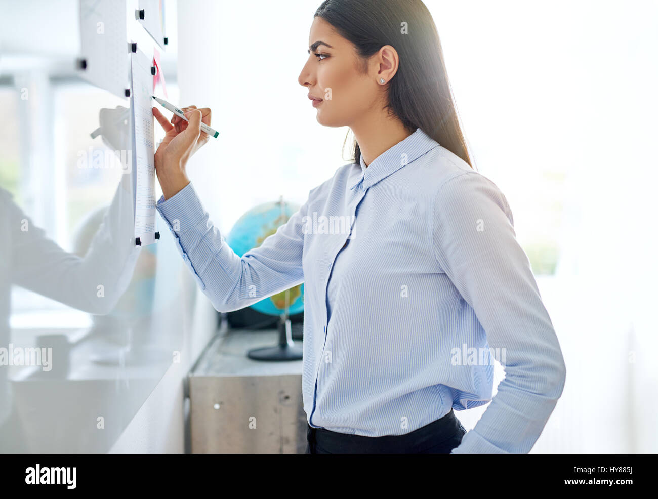 Side view on serious young adult woman in long sleeve blue blouse giggling while writing on white board with bright - Stock Image