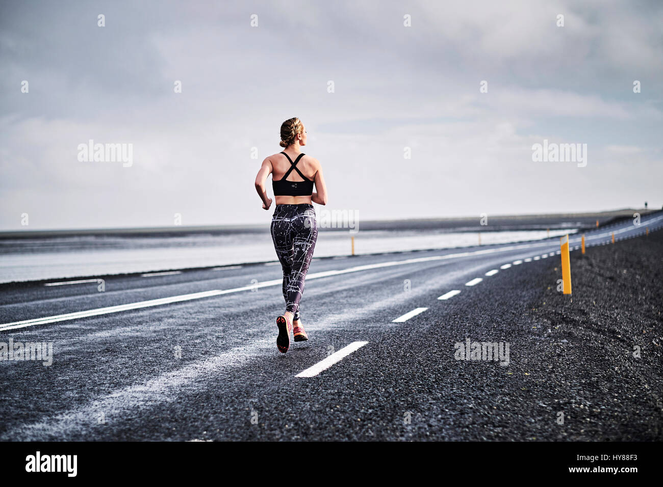 Young women running on a deserted road in Southern Iceland - Stock Image
