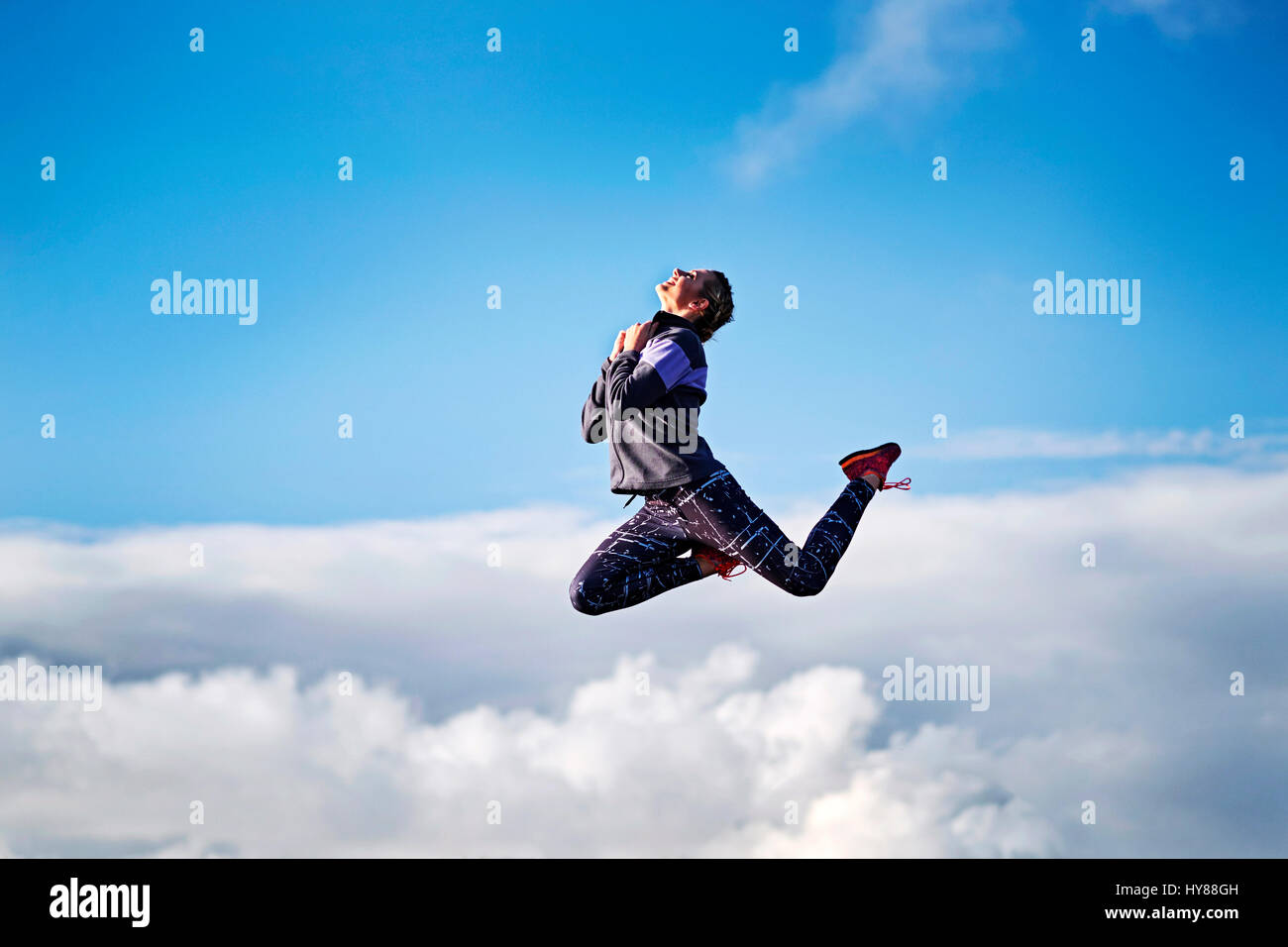 Young women leaping into what appears to be above the clouds in Southern Iceland - Stock Image