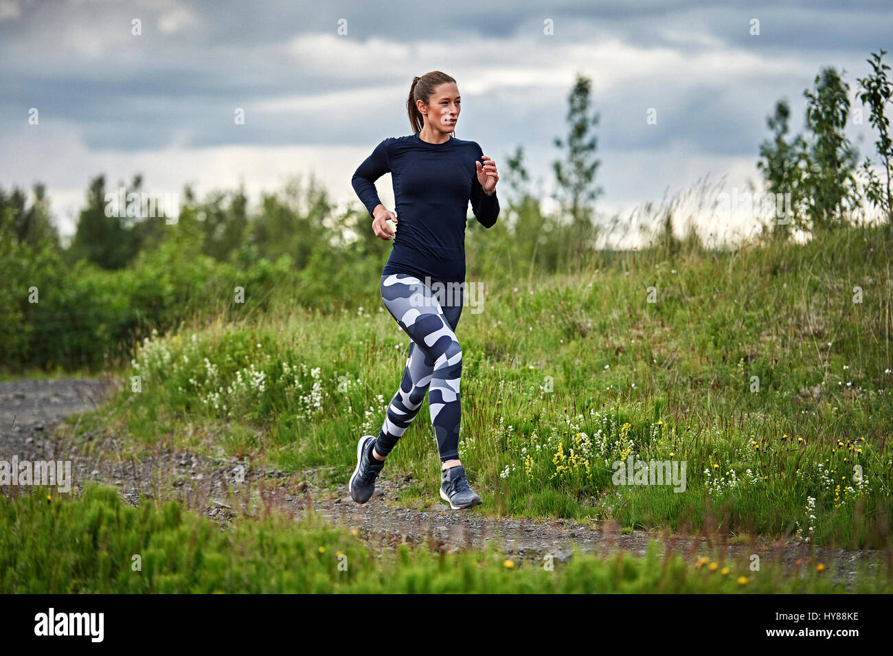 Happy confident young women running on an unmade road in southern Iceland - Stock Image