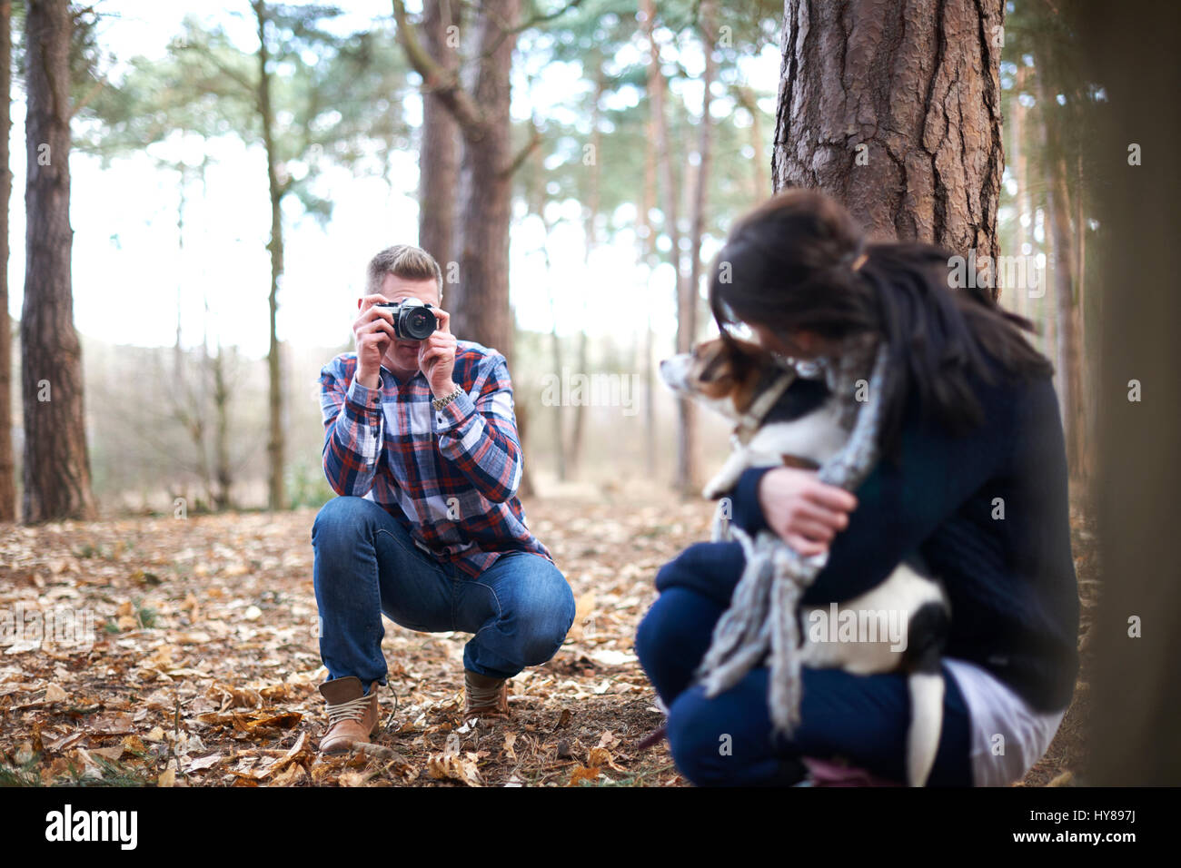 A man takes a photo of his female companion and her dog as they walk in the woods Stock Photo