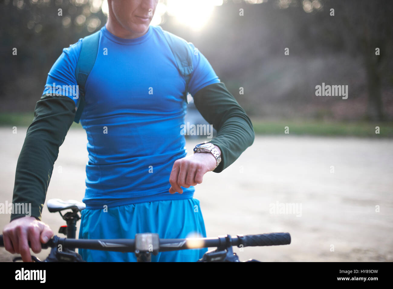 A man checks his watch before going mountain biking - Stock Image