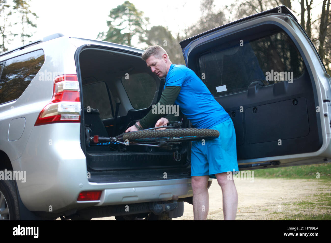 A man puts his mountain bike back in the car after exercise - Stock Image