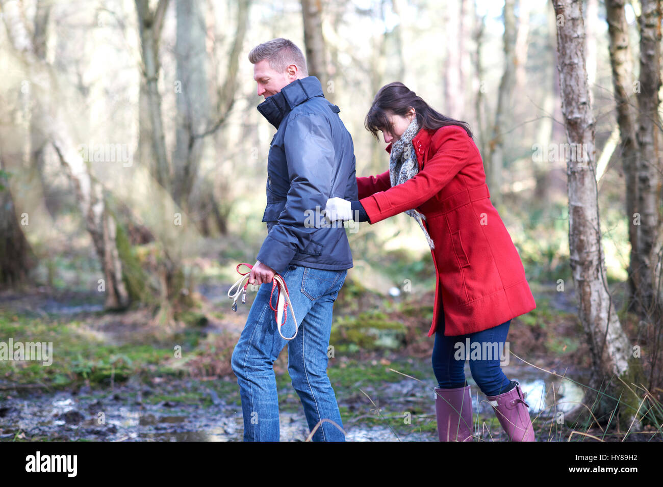 A young couple navigate the mud on a walk in the woods - Stock Image