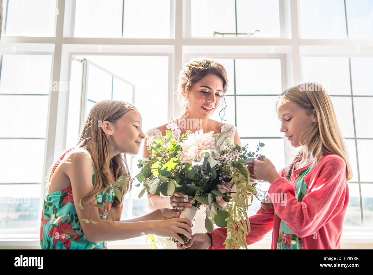 A bride with her twin bridesmaids holding a bouquet of flowers prior to her wedding Stock Photo