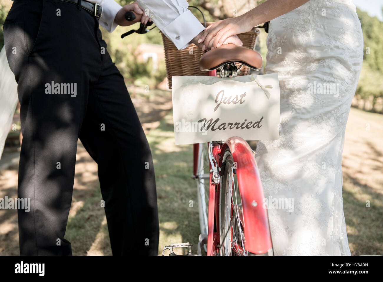 A bride and groom push a bicycle with a Just Married sign on the back - Stock Image