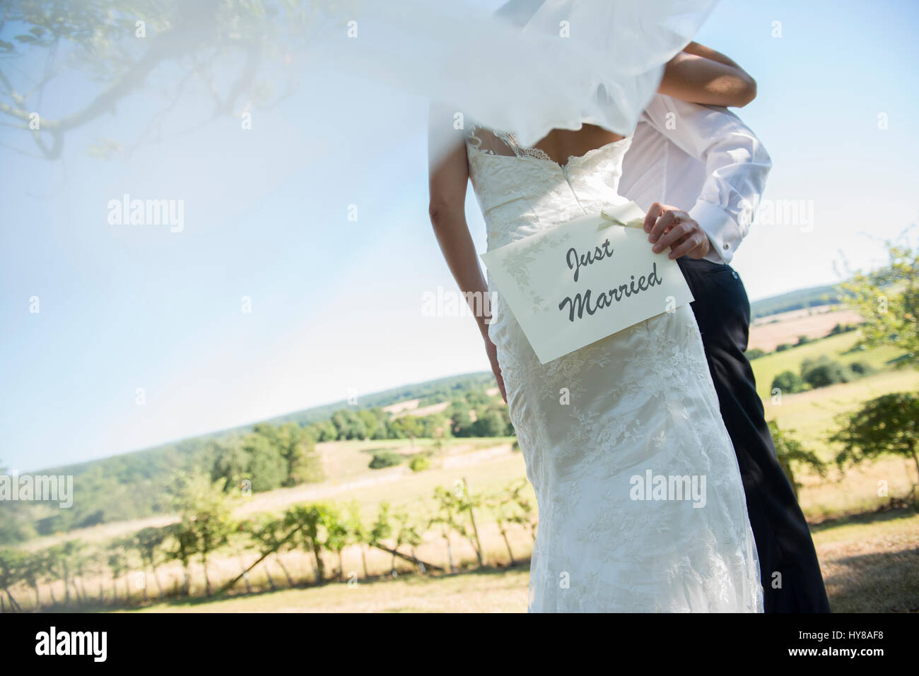 A bride and groom hold a Just Married sign on their wedding day - Stock Image