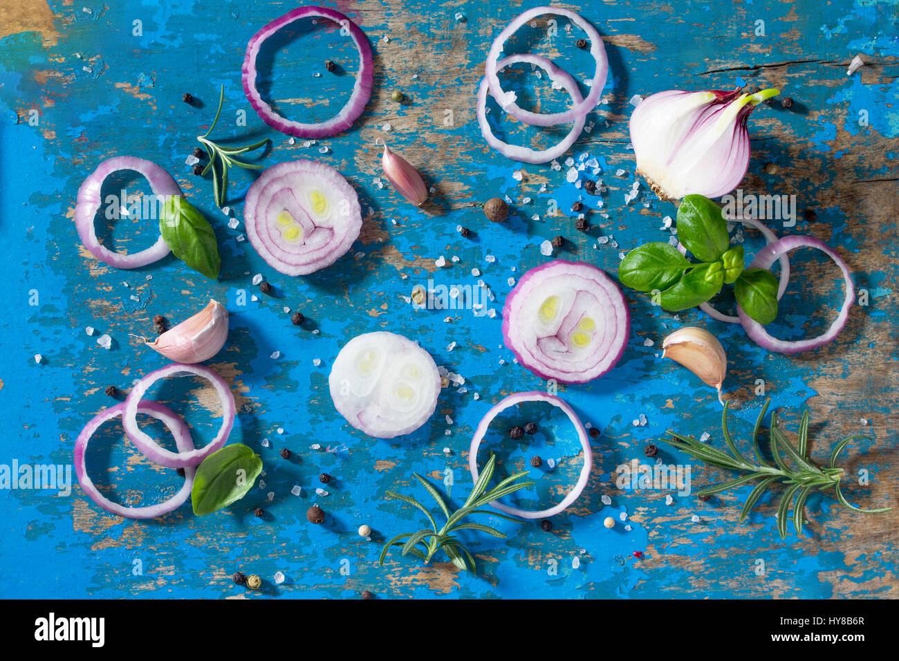 Blue vintage background of cooking with onions, garlic, fresh herbs ...