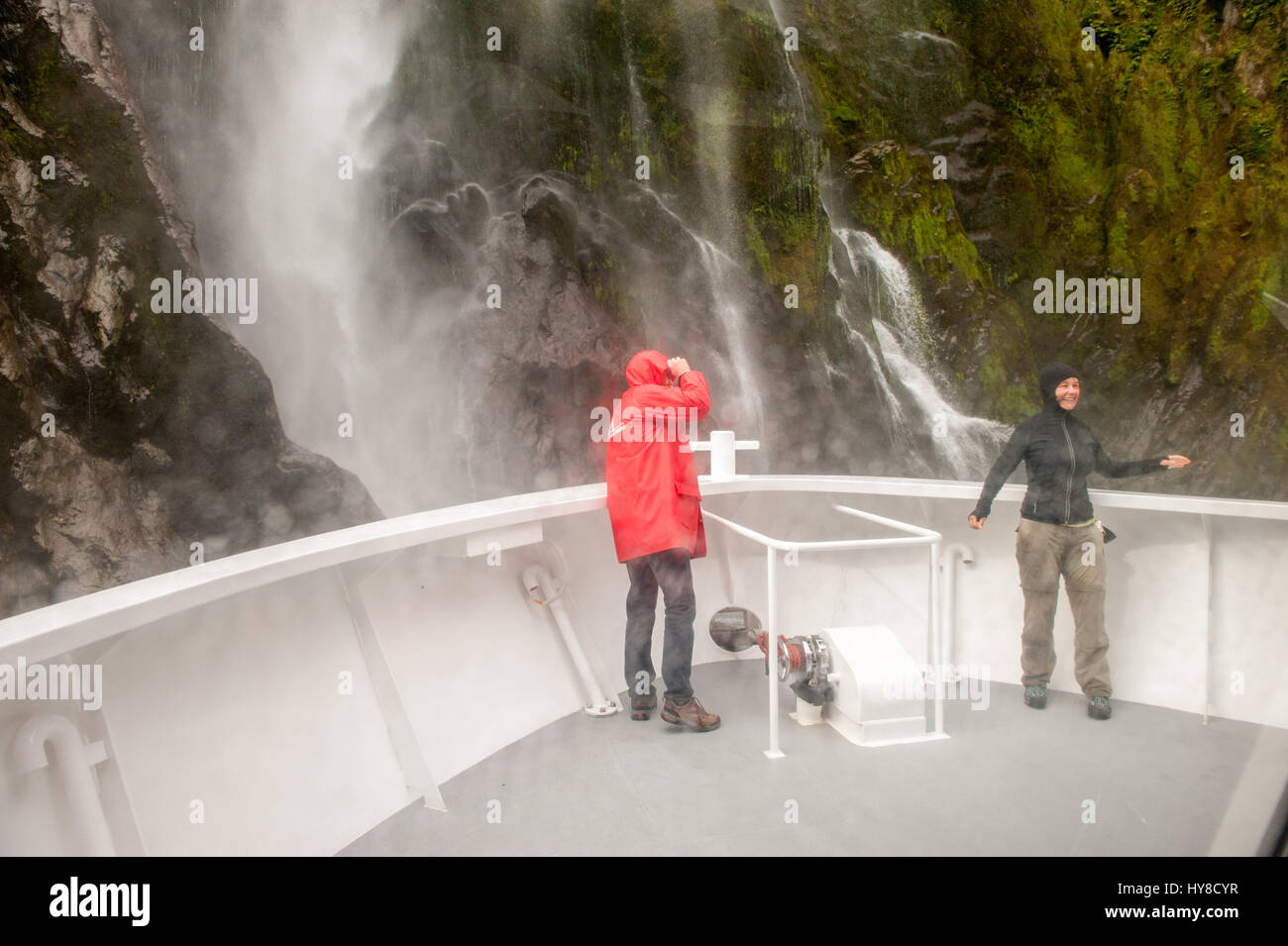 Tourists cruising near a waterfall in Milford sound, Fiordlands National Park, New Zealand Stock Photo