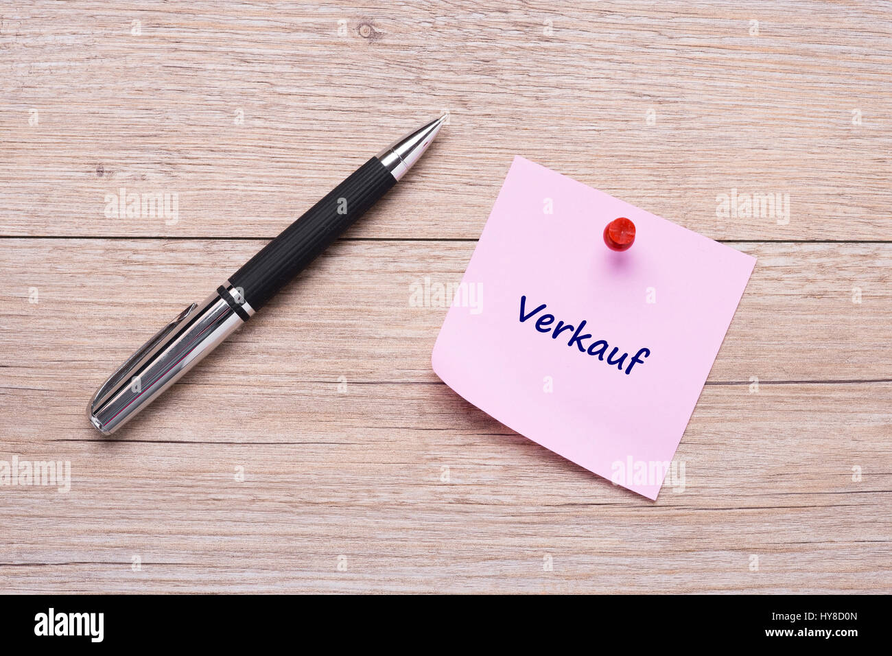 German word for sales 'Verkauf' on pink sticky note and wooden board - Stock Image
