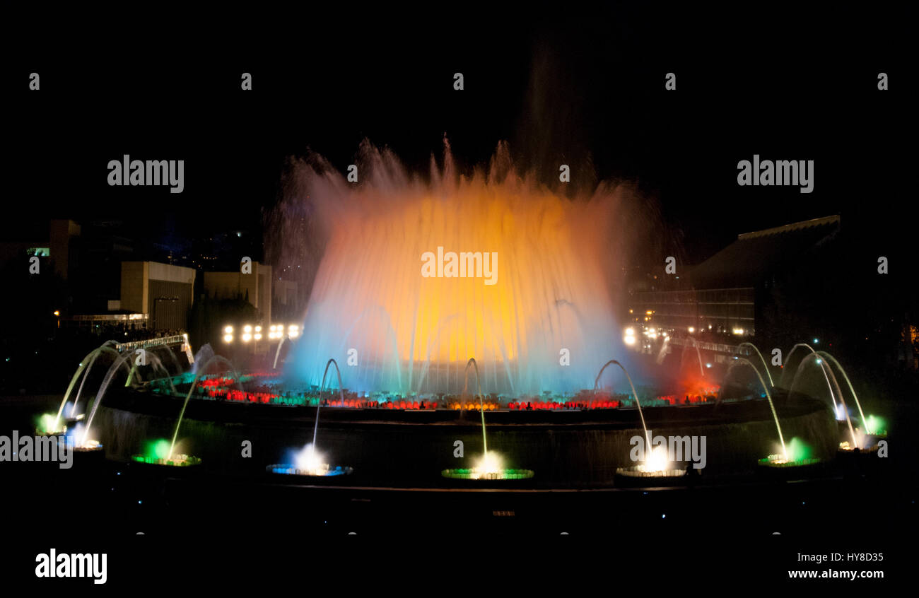 People attend colourful light & water fountain show.  Night at the Magic Fountain in Barcelona. Attraction turns - Stock Image