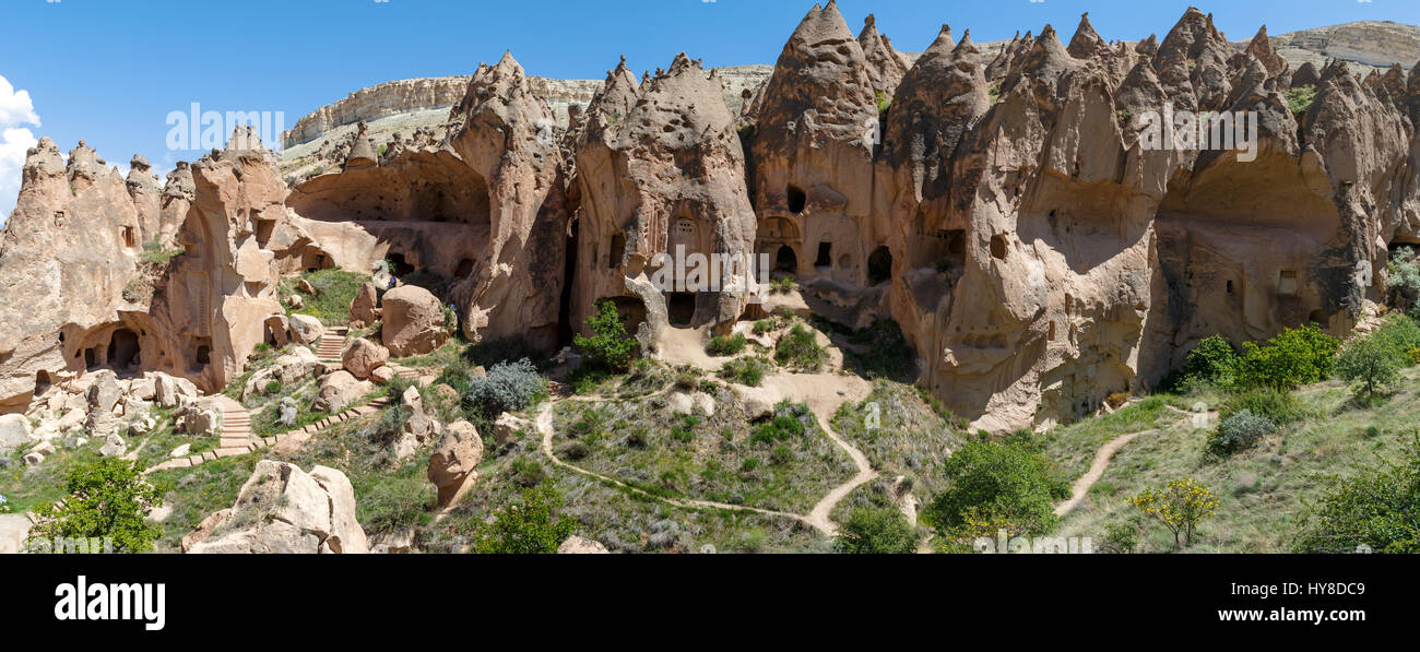 View of famous Zelve Open Air Museum with sandy fairy chimneys and tufa caves in Cappadocia area, on bright blue - Stock Image