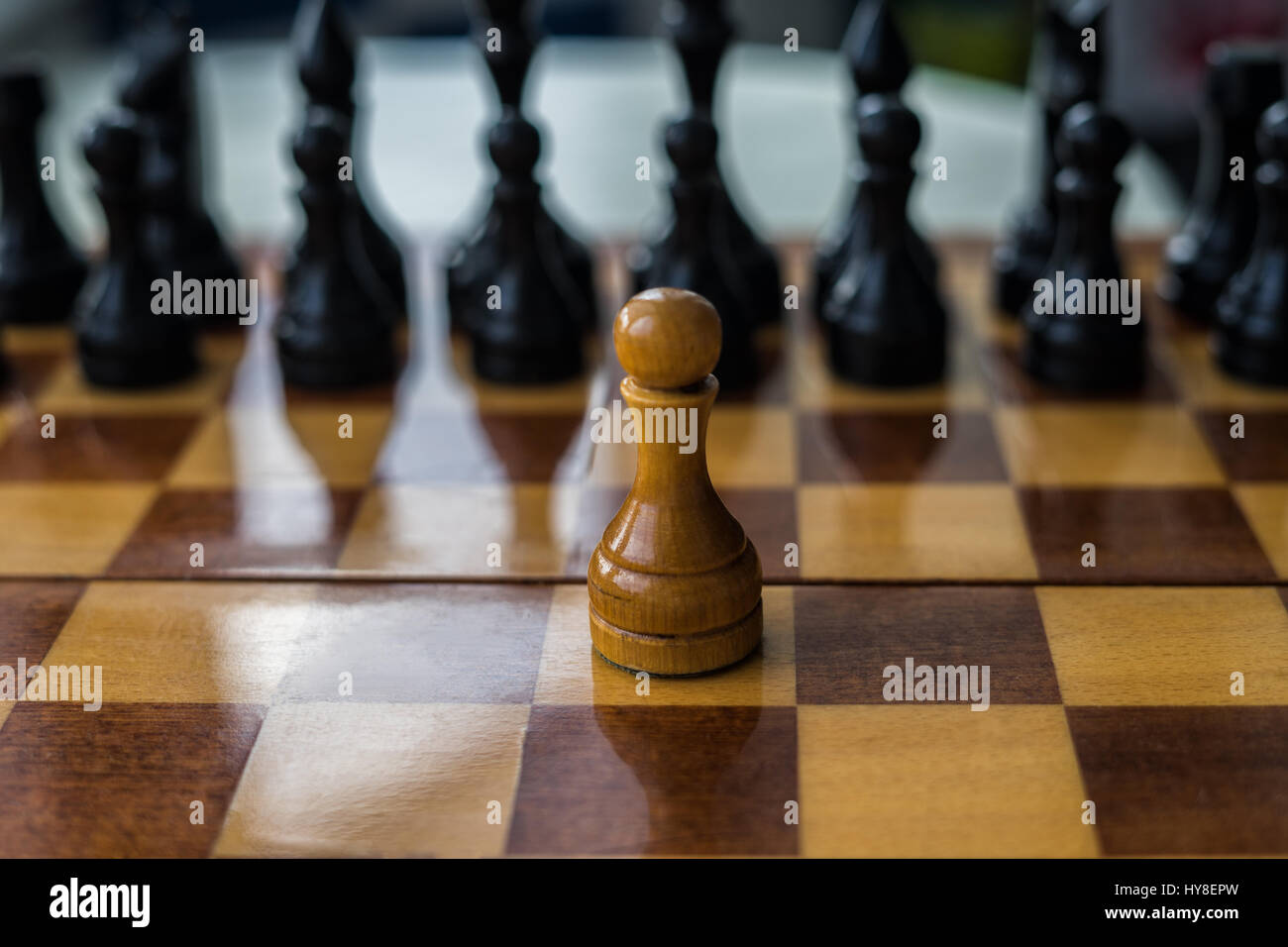 White chess pawn alone on a chessboard. conceptual photo of fighting alone and overcome the life difficulties alone. - Stock Image