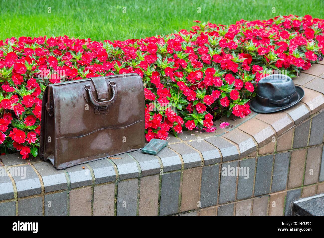 Richmond, Virginia.  Public Sculpture: Forgotten Briefcase, Calculator, and Hat.  Park Sterling Bank Gardens. - Stock Image