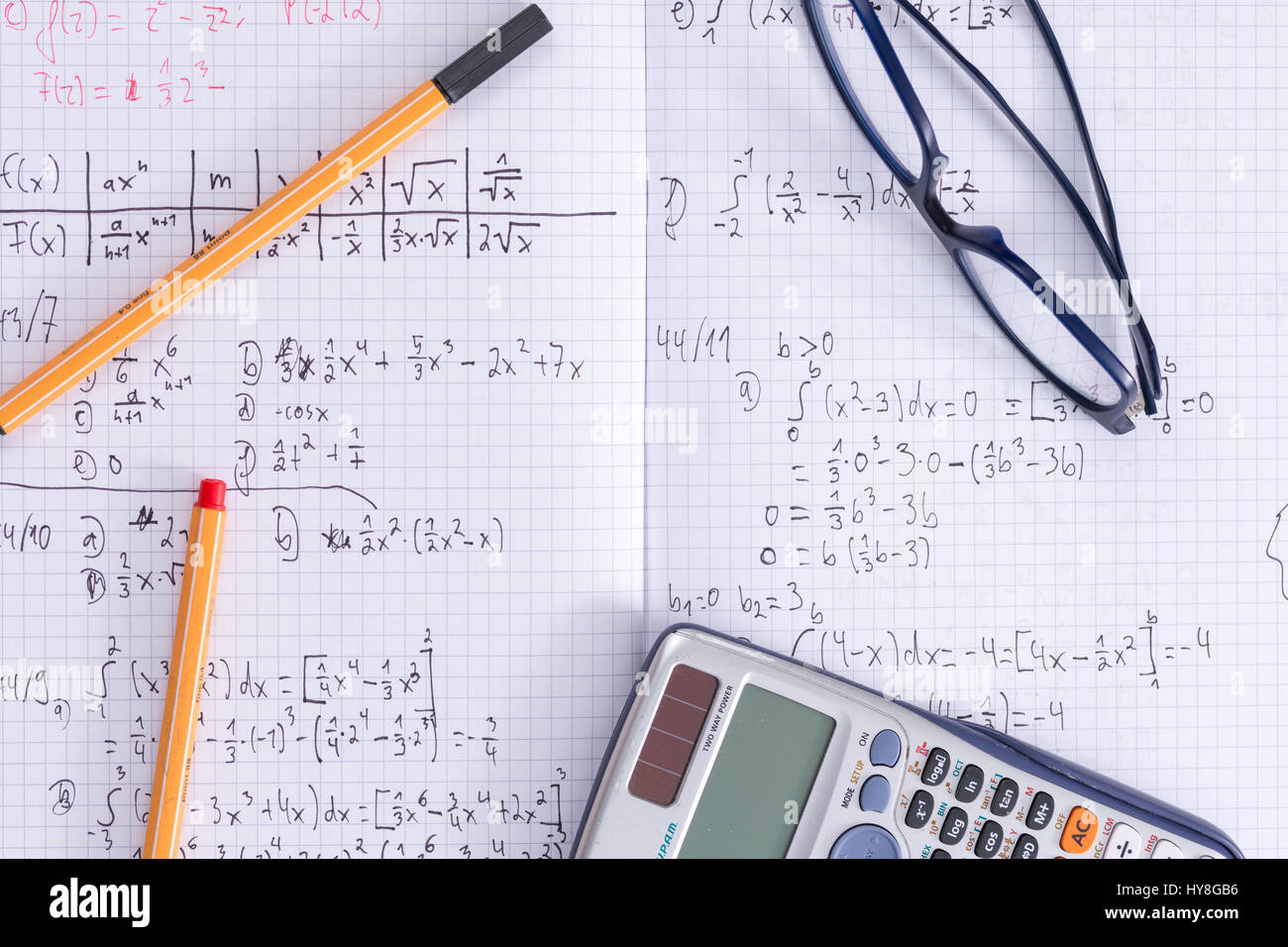 A desk with an exercise book, glasses, pens and a calculator for ...
