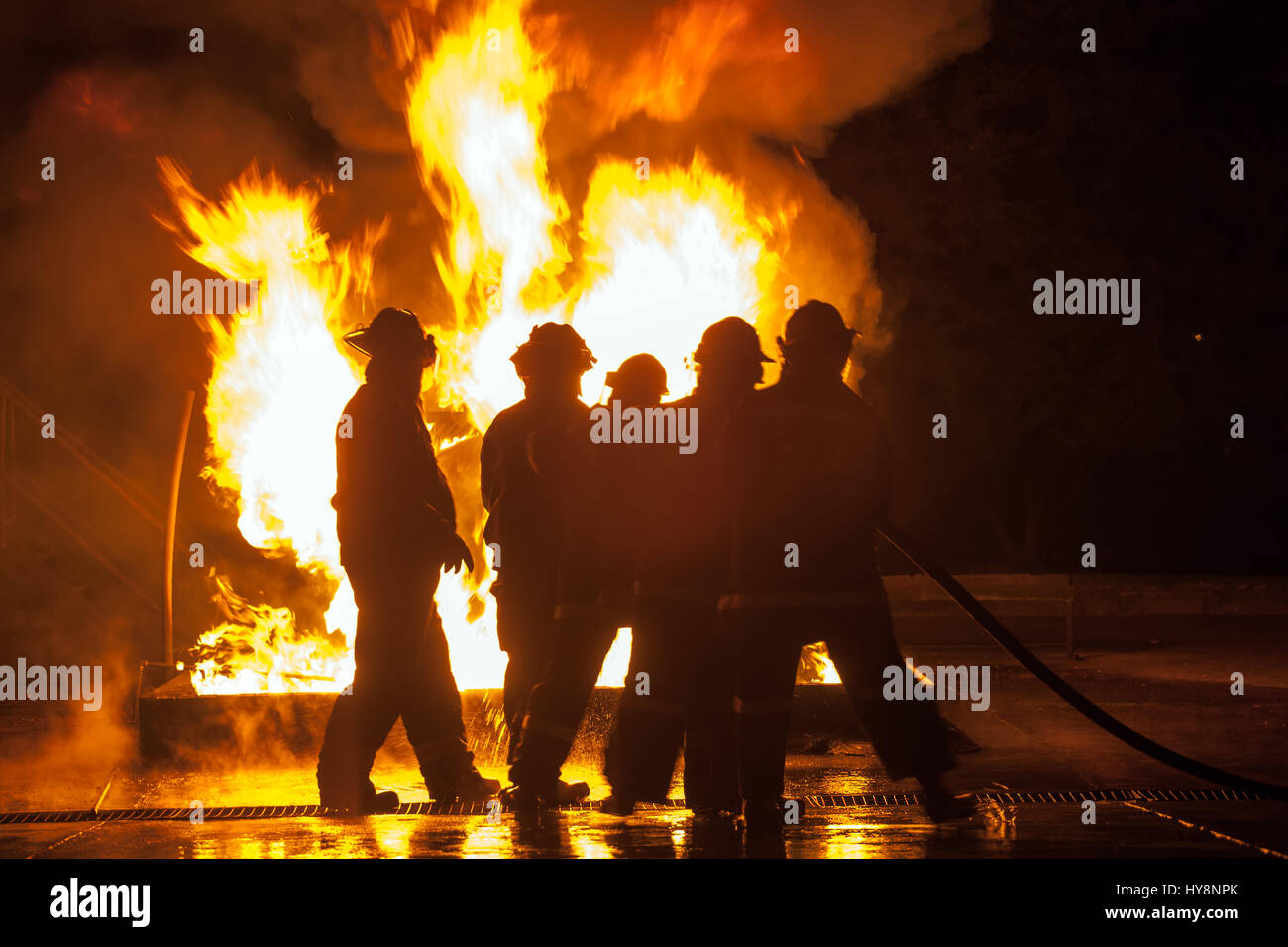 Group of firefighters hosing down burning tank durning firefighting exercise Stock Photo
