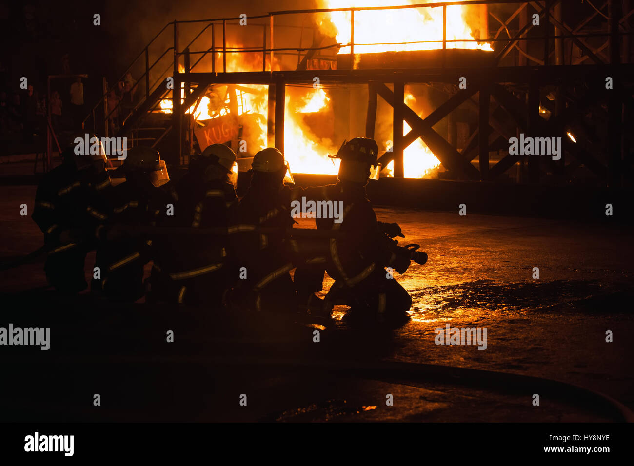 Group of firefighters kneeling in preparation to fight fire in firefighting exercise Stock Photo